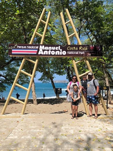 dr key her husband and daughter in front of the sign for manuel antonio costa rica national park.