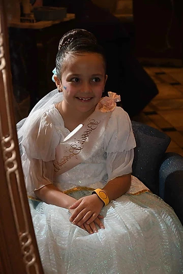 girl in a white dress with a pink sash sitting in a black chair